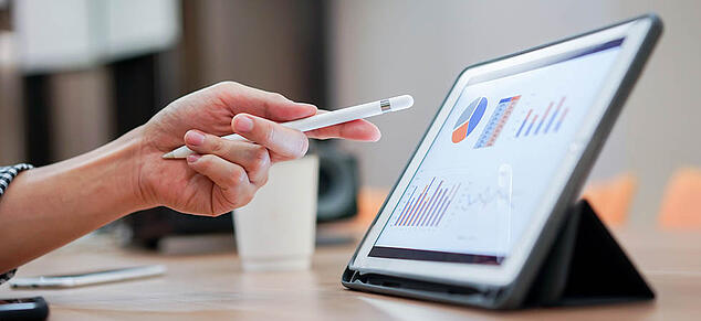 person pointing stylus at ipad of financial charts