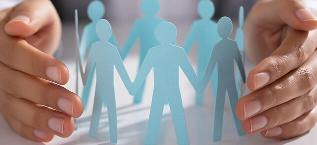 GettyImages_hands around blue paper cut out people_980x450