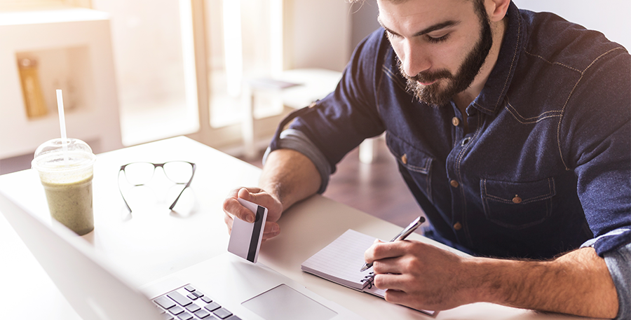 Man in a denim short sitting at a desk while jotting down notes in his note pad with a credit card in the other hand
