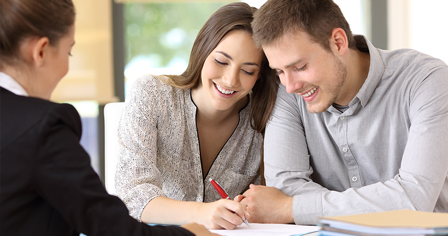 a couple happily signing a contract with a red pen while sitting across from a woman in a suit