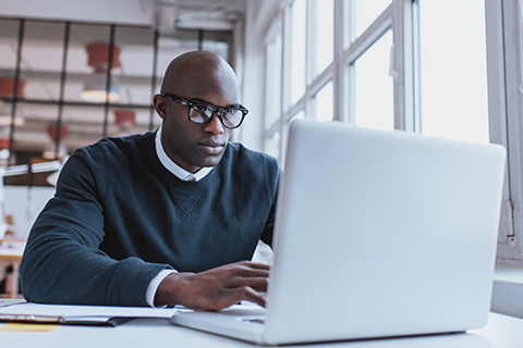 Man in sweater and glasses sitting and typing at a laptop computer