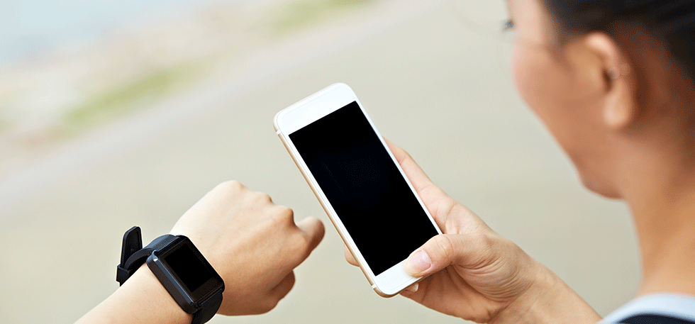 Woman looking at her black smart watch and white smart phone