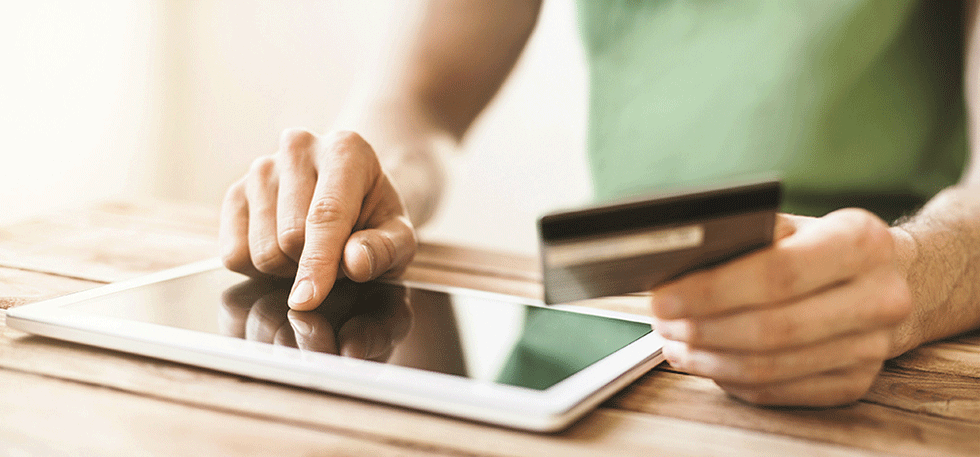person holding a credit card while tapping an tablet