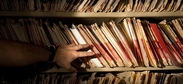 Man Hand with Flashlight looking at Medical Records_GettyImages_980x450