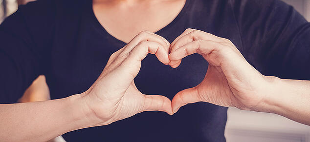 Woman Forming Heart with Hands_GettyImages_980x450
